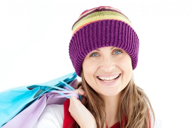 Femme souriante tenant des sacs à provisions