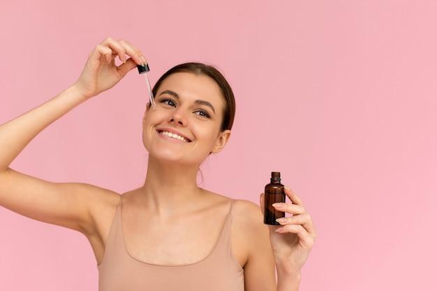 Femme souriante tenant un sérum de vitamine c près de son visage sur fond rose. concept de soins de la peau et de santé.