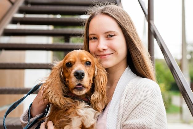 Femme souriante tenant son chien