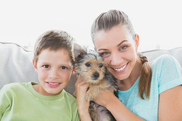 Femme souriante tenant son chiot yorkshire terrier avec son fils