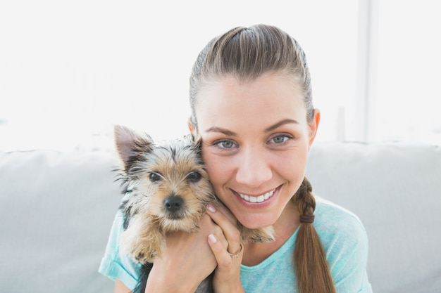 Femme souriante tenant son chiot yorkshire terrier