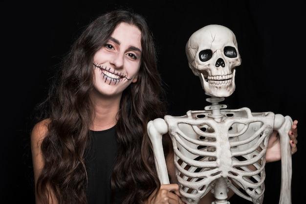 Femme souriante tenant squelette