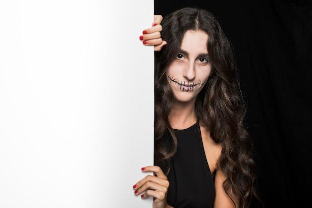 Femme souriante tenant tableau blanc