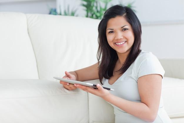 Femme souriante tenant une tablette tactile devant un canapé