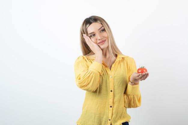Femme souriante tenant une tomate rouge et posant sur un mur blanc.