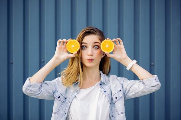 Femme souriante, tenue, deux, orange, dans, mains