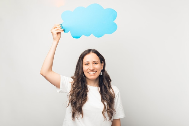 Une femme souriante tient un nuage de papier bleu au-dessus de sa tête.