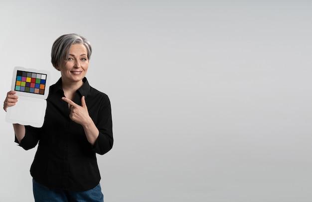 Femme souriante tient un vérificateur de couleur pointant dessus
