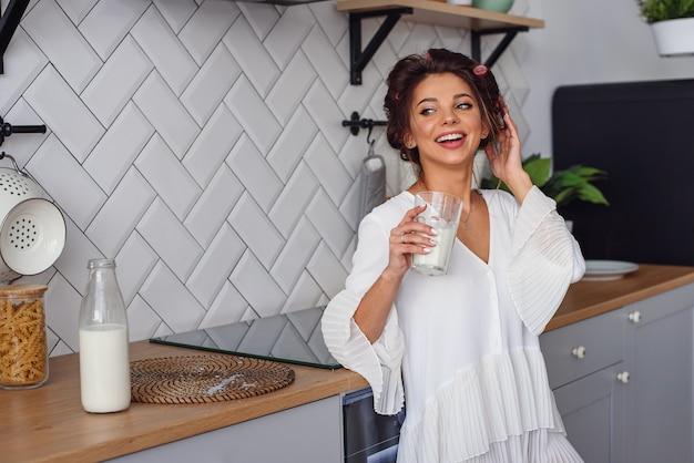 Femme souriante tient un verre de lait frais, dans l'élégante cuisine confortable du matin. une alimentation saine et une alimentation saine, concept végétarien.