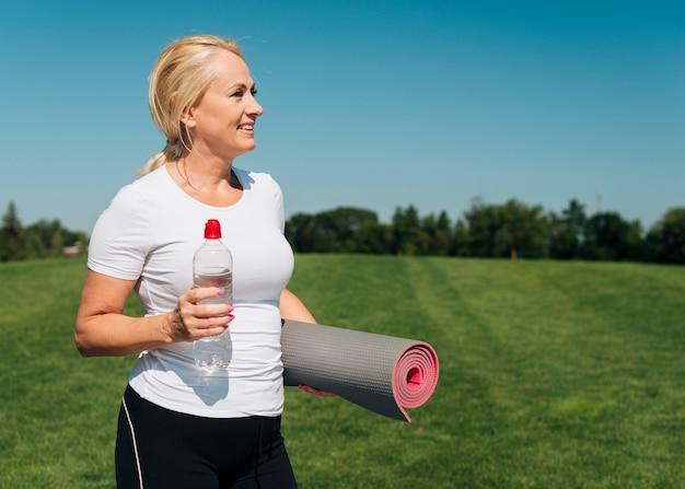 Femme souriante tir moyen avec tapis de yoga