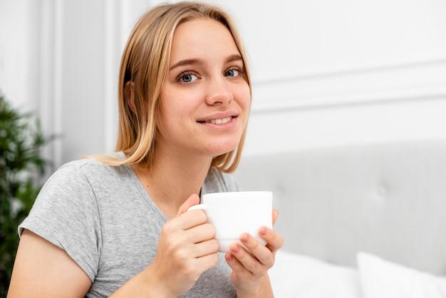 Femme souriante tir moyen avec tasse