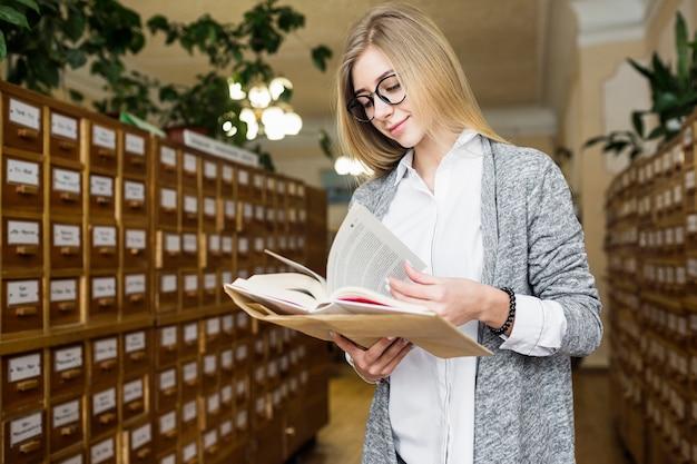Femme souriante, tournant les pages du livre