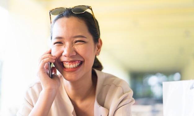 Femme souriante tout en parlant de smartphone en temps de liberté