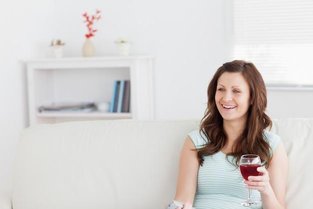 Femme souriante tout en tenant un verre de vin