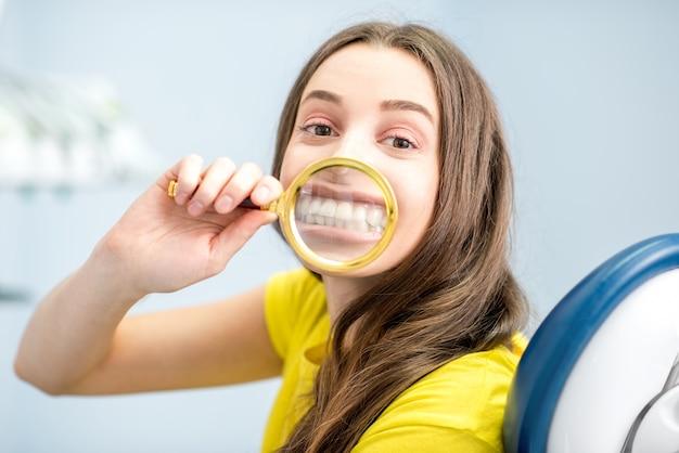 Femme souriante à travers la loupe assise au cabinet dentaire