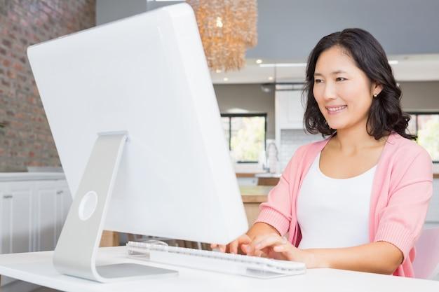 Femme souriante utilisant un ordinateur à la maison