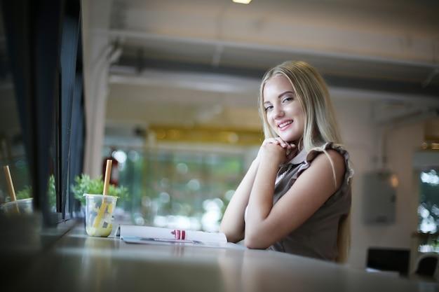 Une femme souriante utilisant un ordinateur portable sur son lieu de travail pour les petites entreprises cherchant à engager le public et à faire évoluer la création de contenu peut adopter une nouvelle technologie de marketing dans l'espace de travail. notion de pigiste.