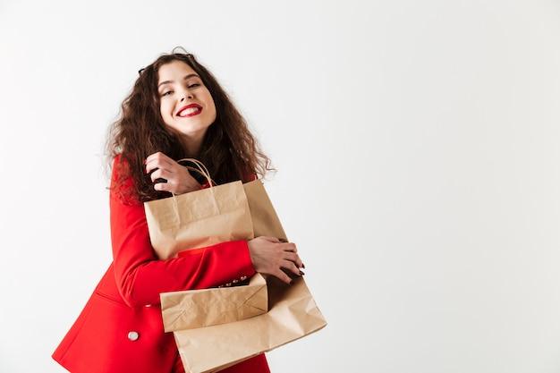 Femme souriante de vente tenant des sacs à provisions