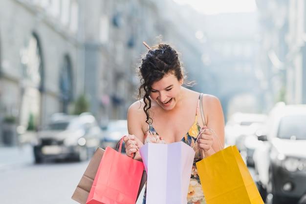 Femme souriante, vérifiant ses sacs à provisions