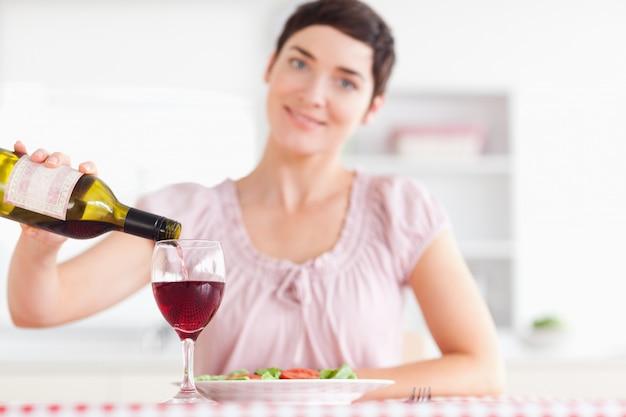 Femme souriante versant le vin rouge dans un verre