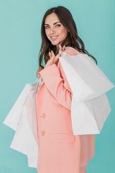 Femme souriante en veste rose en regardant la caméra