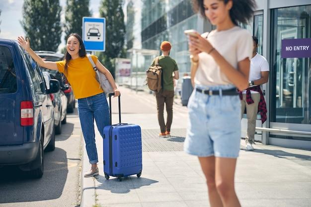Une femme souriante en vêtements décontractés est arrivée en ville en avion alors qu'elle se tenait à l'extérieur et s'arrêtait en taxi à l'aéroport