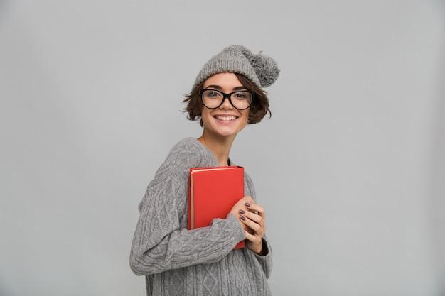 Femme souriante, vêtue d'un pull et d'un chapeau chaud tenant un livre.
