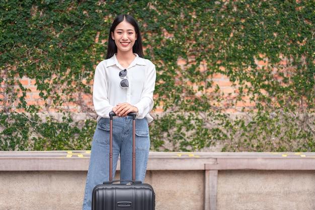 Femme souriante voyageur traînant un sac à bagages valise noire marchant jusqu'à l'embarquement des passagers à l'aéroport, concept de voyage.