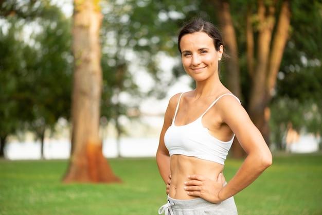 Femme souriante vue de côté avec les mains sur les hanches