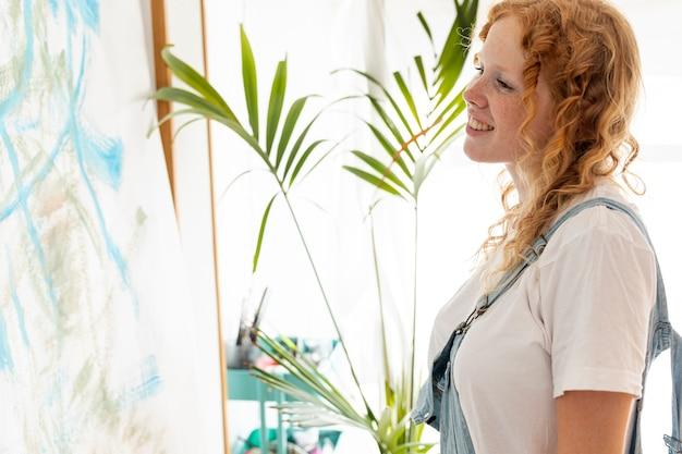 Femme souriante vue de côté en regardant un mur