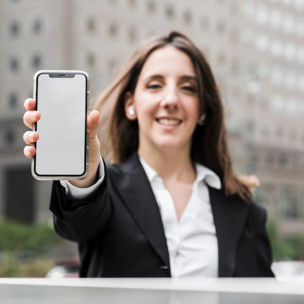 Femme souriante vue de face, levant son téléphone