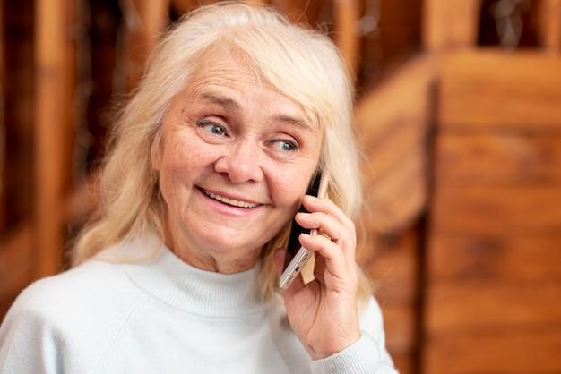 Femme souriante vue de face parler au téléphone