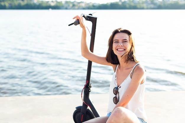 Femme souriante vue de face posant sur un scooter