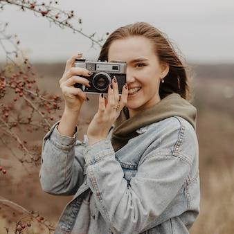 Femme souriante vue de face prenant des photos