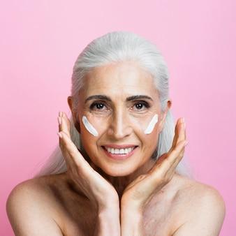 Femme souriante vue de face avec un produit de soin de la peau