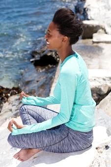 Femme souriante de yoga afro-américain assis près de l'eau