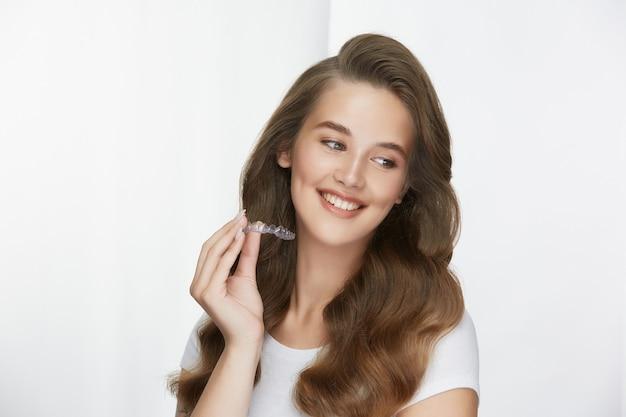 Femme avec un sourire blanc parfait tenant le capuchon de la dent et à la recherche de côté