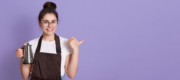 Femme avec un sourire charmant portant des lunettes, un t-shirt décontracté et un tablier marron, pointant de côté avec le pouce