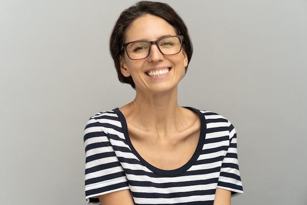 Femme avec un sourire à pleines dents porter des lunettes et une chemise rayée
