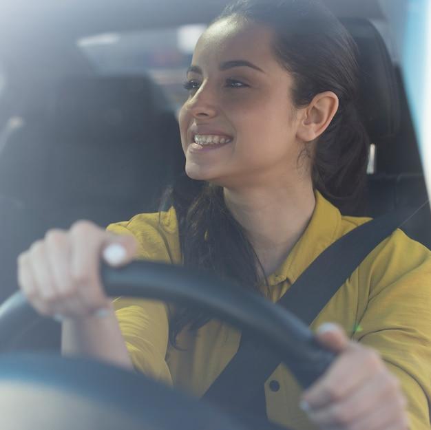 Femme sourit et regarde dans le rétroviseur