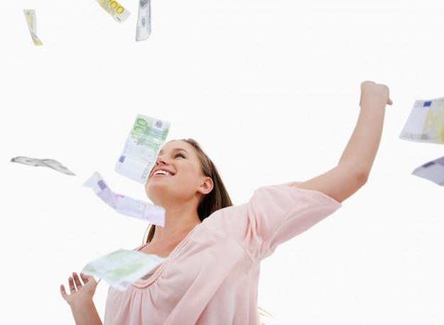 Femme sous les billets de banque tombant