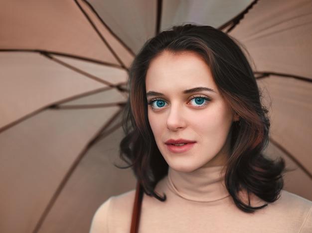 Femme sous un parapluie beige