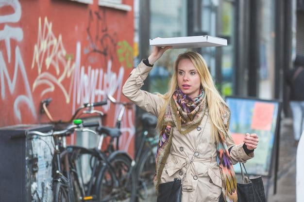 Femme sous la pluie recouvrant une pizza à copenhague