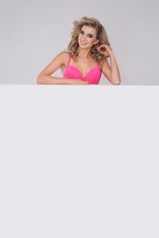 Femme en sous-vêtements roses debout derrière le tableau blanc