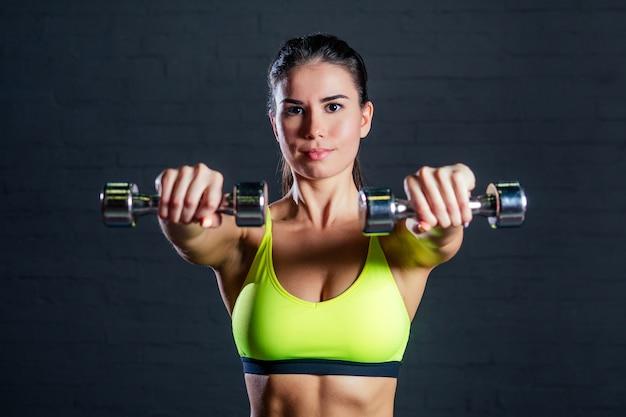 Femme en soutien-gorge de sport vert engagé dans une salle de sport à l'aide d'haltères sur fond de briques noires
