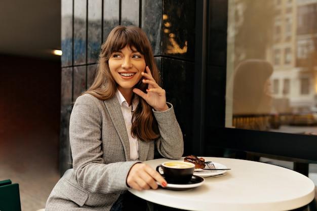 Femme spectaculaire aux cheveux longs foncés souriant pendant la pause-café.