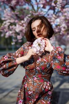 Une femme spectaculaire vêtue d'une robe brillante se dresse sur fond de sakura. une femme brune dans une belle tenue sourit dans la rue en marchant