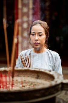 Femme spirituelle avec de l'encens brûlant au temple