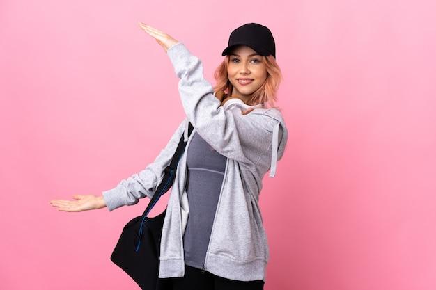 Femme de sport adolescent avec sac de sport sur fond isolé tenant copyspace pour insérer une annonce