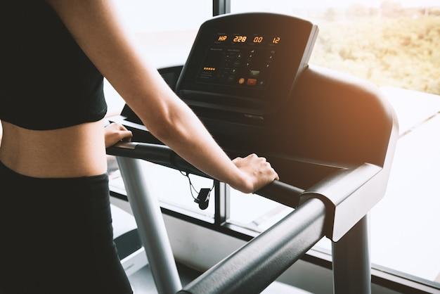 Femme de sport asiatique marchant ou en cours d'exécution sur l'équipement de tapis roulant dans la salle de gym d'entraînement de remise en forme